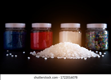 White plastic and blue plastic beads in plastic bottles on black background, Polymers bead or polymer resin, polymer pallet, Product from petrochemical plants.