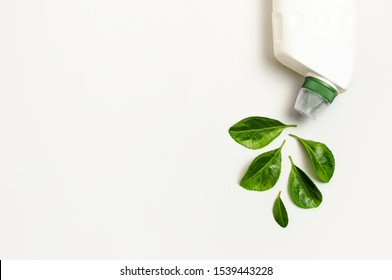 White plastic bottle for liquid detergent, cleaning agent, bleach, antibacterial gel with natural plant extract and green leaves on white background. Eco style cleaning concept. Flat lay top view