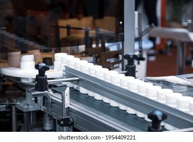 White plastic bottle on capsule filling machine conveyor belt in production line. Pharmaceutical industry