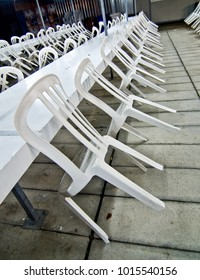 white plastic chairs leaning against the tables after the end of the cleaning party