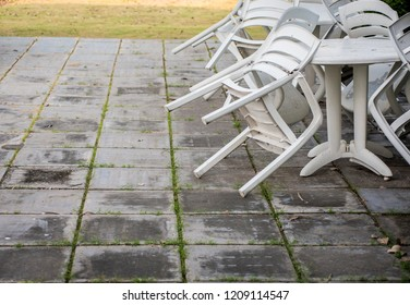 White plastic chairs stacked with white plasti tables on concrete blocks