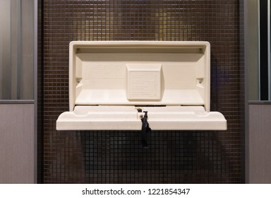white plastic diaper table on brown ceramic wall in toilet. Baby diaper table in a public restroom