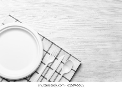 White plastic disposable tableware on wooden background