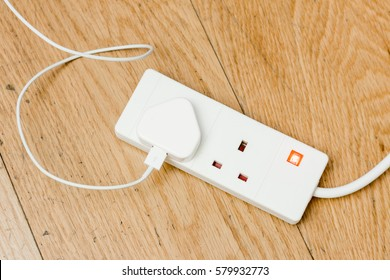 A white plastic extension power cord from united kingdom. One cable attached to it.