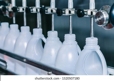 white plastic gallons or bottle on the production line of the conveyor at filling machine in the factory. selective focus. industrial and technology concept.