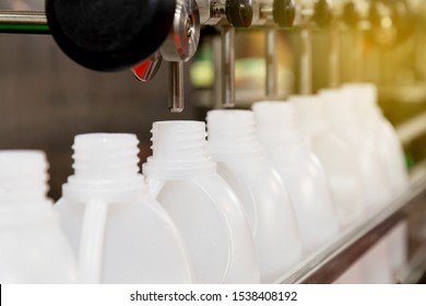 white plastic gallons or bottles on the production line of the conveyor at filling machine in the factory with sunbeam in the morning. selective focus. industrial and technology concept.