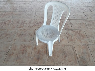 white plastic garden chair standing on paved patio.