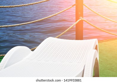 White plastic lounge chair on a green pier with sea and sunlight