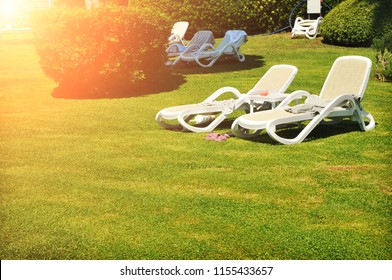 White plastic lounge chairs at the park with green grass and bushes with sunllight