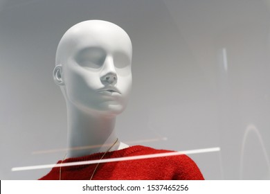 White plastic mannequin of a girl in a red sweater. Portrait of a mannequin behind glass on a shop window of a clothing store.