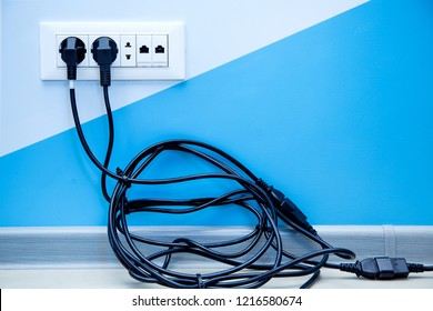 a white plastic multiple outlet mounted on a light wall with copy space for text, plugs with a twisted pile of black cable are included in the socket.