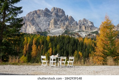 White plastic picnic table stands full underneath a scenic rocky ridge in the Italian Alps. Picturesque shot a small table and chairs set on a patch of gravel offering a breathtaking view of Dolomites