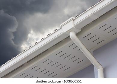 white plastic rain gutter and dark sky. concept : preparing maintenance rain gutter before rainy season.