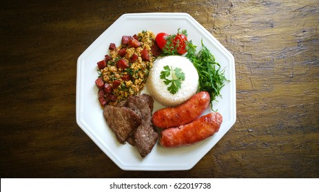 White plate with barbecue, calabresa, rice, tropeiro beans and cabbage top view