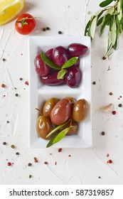 White plate with black and green olives with olive branch on a white abstract background with lemon, cherry tomato, spices. Healthy food. Greek food. Mediterranean food