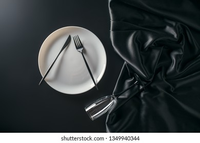 White plate with black tableware on black table. White plate on black background, top view