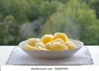 A white plate of boiled potatoes. The boiled potatoes. Potatoes couple. Plate on a white napkin. Green background