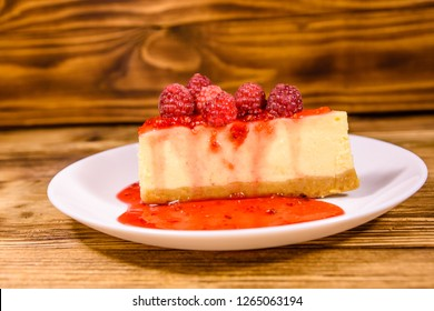 White plate with cheesecake New York and raspberries on rustic wooden table