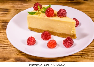 White plate with cheesecake New York, leaf of mint and raspberries on rustic wooden table