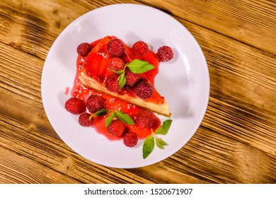 White plate with cheesecake New York, leaves of mint and raspberries on rustic wooden table. Top view