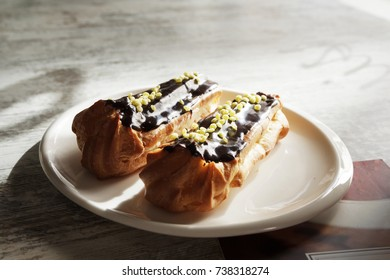 White plate with chocolate eclairs on wooden table. Top view.