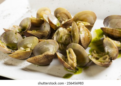 White plate with clams and green sauce