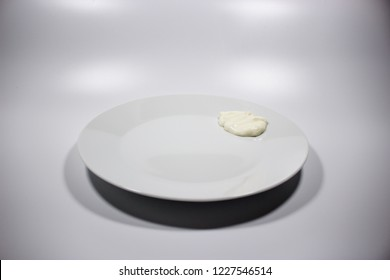 White plate with cream sauce, isolated