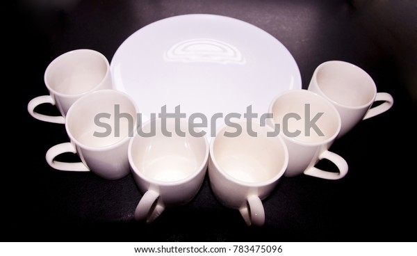 white plate and a lot of cups around it