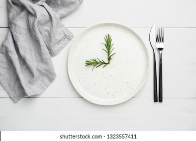 White plate and cutlery on white wooden planks, food background. Concept of meal time, restaurant food serving, abstract clock.