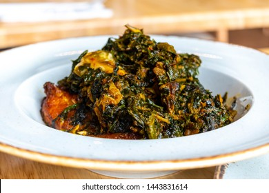 A white plate of Egusi soup on a white background. Nigerian food: A bowl of Efo Riro soup, vegetable soup