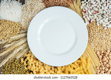 White plate and foods high in carbohydrate on wooden background. Pasta, chickpeas, mung, lentil, rice, buckwheat, beans, pearl barley and oats.