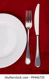 White plate, fork and knife on red background.