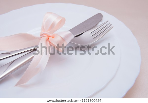 White plate, fork and knife on light background.