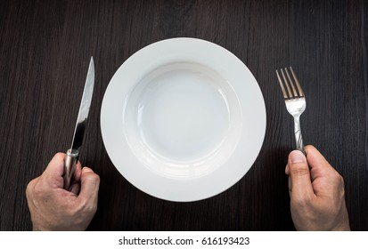 White plate, fork , knife, preparation equipment to wait for the meal. And have a hand waiting to prepare food and catch equipment.
