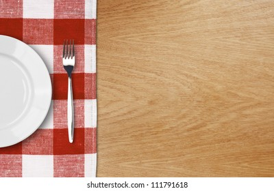 white plate and fork on wooden table with red checked tablecloth and copyspace