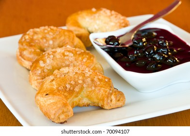 White plate of freshly baked, golden croissants with a bowl of blackberry jelly and a spoon