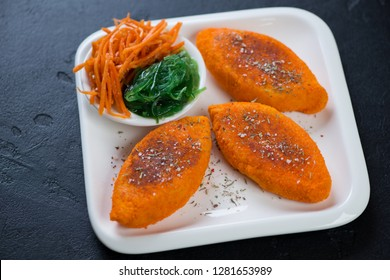 White plate with fried carrot cutlets over black stone background, studio shot