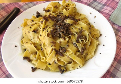 White plate full of fresh pasta with truffles, in Italy