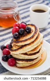 white plate full of pancakes with berries and honey on a wooden background