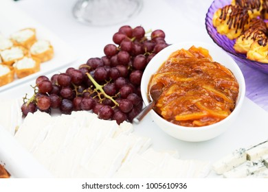 White plate with grapes, fresh cheese and bowl of dip. Summer outdoor wedding.