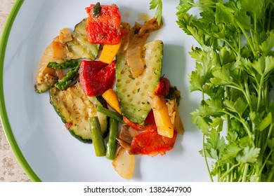 A white plate with grilled vegetable and parsley. From above.