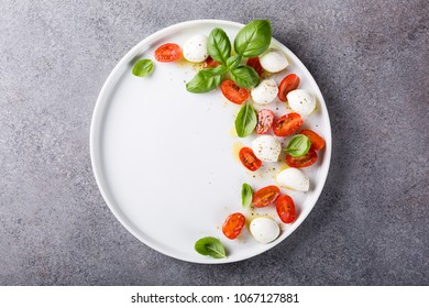 White plate of healthy classic delicious caprese salad with ripe tomatoes and mozzarella cheese with fresh basil leaves on gray concrete background with space for text. Italian food. Top view.