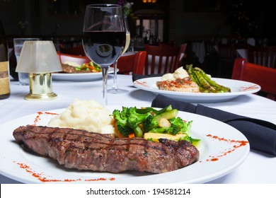 A white plate holds a delicious grilled New York Strip Steak with a side of mashed potatoes and fresh mixed vegetables.  A glass of red wine completes the meal.