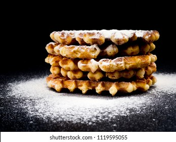 White plate with homemade Belgian waffles, on top of poured sifting of powdered sugar on black background, very tasty snack. sugar over old wooden table. Dark rustic style. copy space, stylish.