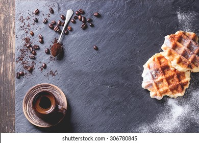 White plate with homemade belgian waffles with sugar powder, ceramic cup of coffee, teaspoon and coffee beans. Over black slate as background. With copy space at centre. Top view.