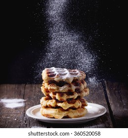 White plate with homemade belgian waffles with Sifting sugar powder over black background. sugar powder over old wooden table. Dark rustic style. Square image with selective focus