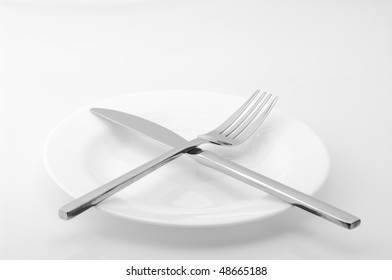 White plate, knife and fork on light background. Monochrome image.