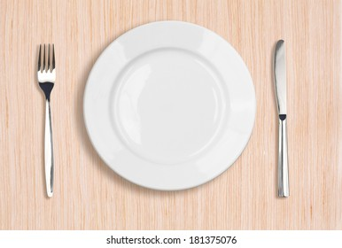 white plate, knife and fork top view on wooden table
