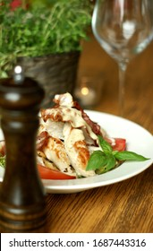 White plate of meal with fried chicken and grilled bacon on the fresh green salad with tomato decorated with basil leaf behind the wooden pepper mill and with green yerbs and wine glass in background