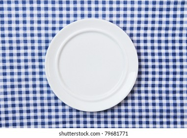 White Plate on Blue and White checkered Fabric Tablecloth Background